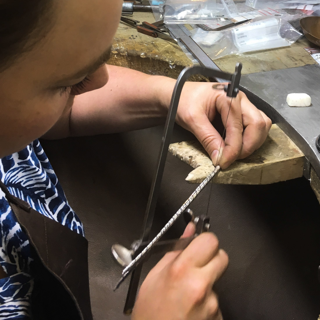 Goldschmiedin arbeitet am Werkbrett